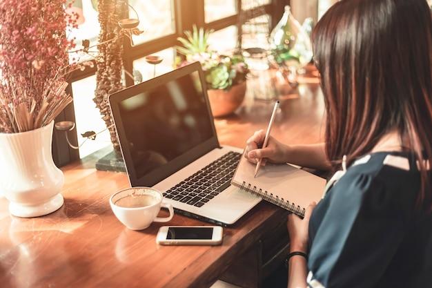 働くアジアビジネス女性ノートとノートパソコンでメモをとる Premium写真