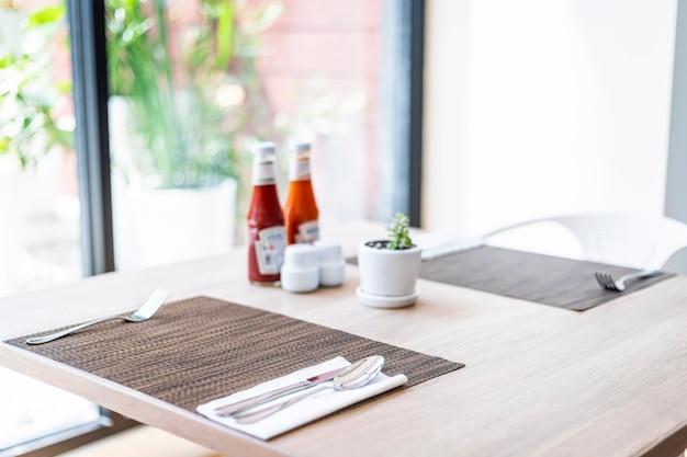 豪華なスプーンとフォーク、花瓶、ソースのクローズアップは、ホテルのダイニングテーブルの装飾 Premium写真