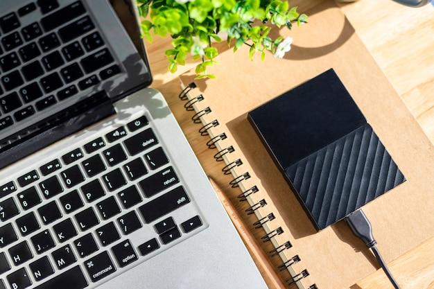 木製の背景、トップビューオフィステーブルに鉛筆とフラワーポットツリーとノートパソコンのキーボードとノートブックの外付けハードディスク。 Premium写真