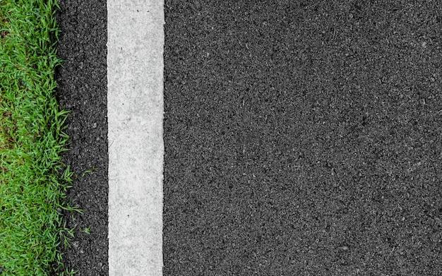 Поверхность гранж неровный асфальт черный темно-серый дорожная улица и зеленая трава Premium Фотографии