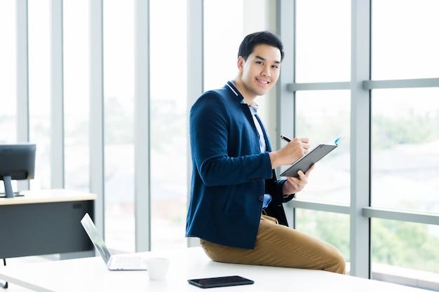 働くアジアの青年実業家を考えて、ビジネスプランノートとラップトップコンピューターに記録されたメモを読んで、オフィスルームのテーブルに座っているスマートフォン。 Premium写真