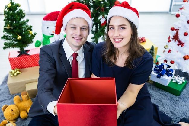 クリスマスのための空のギフトを保持している幸せなカップル Premium写真