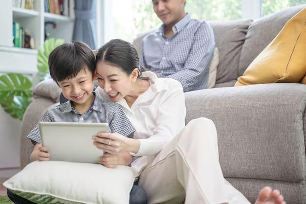 リビングルームのソファで一緒に時間を過ごす幸せなアジア家族。 Premium写真