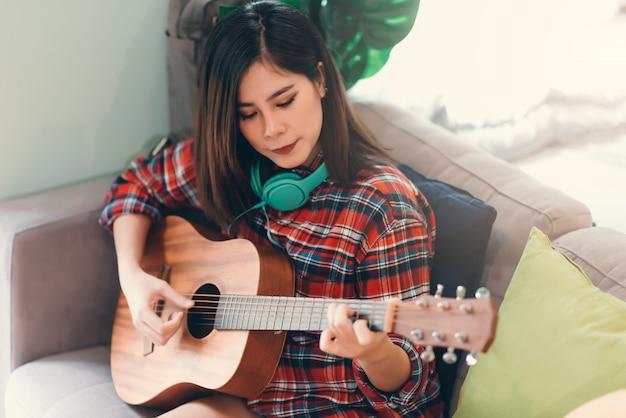 Красивая азиатская молодая девушка битника играя гитару дома для ослабляет Premium Фотографии