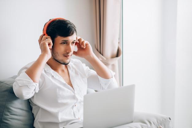 Кавказский молодой красивый деловой человек работает на ноутбуке и носить стерео гарнитуру для прослушивания музыки во время работы из дома Premium Фотографии