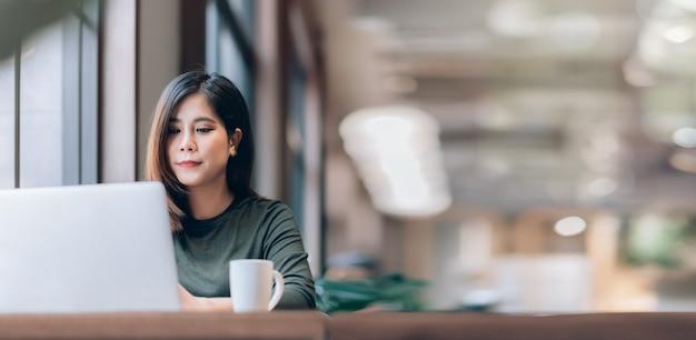 Умная азиатская женщина, внештатная онлайн работа из дома с ноутбуком Premium Фотографии