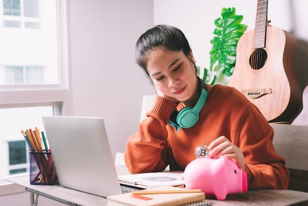 Азиатская женщина, положившая биткойн-монету в розовую копилку для экономии средств - управление финансами или концепция сбережений Premium Фотографии