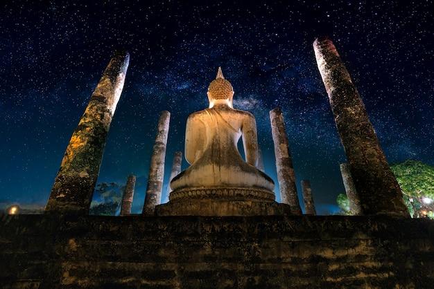 スコータイ歴史公園、タイのワットマハタート寺院で夜の大仏上の天の川。 Premium写真