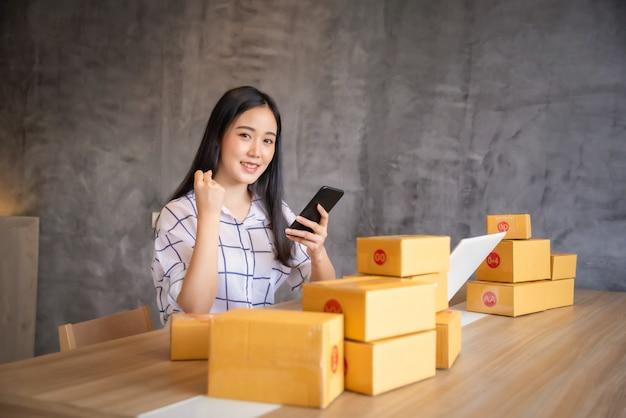 ラップトップコンピューターを自宅でオンラインショッピング若いアジアの肖像画。オンライン販売と配信のコンセプト Premium写真