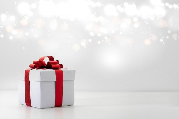 Красная подарочная коробка на белом фоне, рождественские огни боке Premium Фотографии