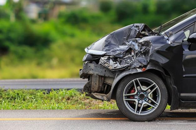 黒い車の前が道路上の事故によって損なわれる Premium写真