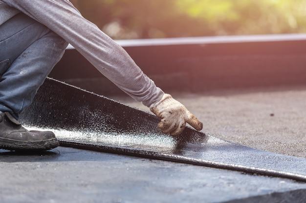 Азиатский рабочий, устанавливающий смоляную фольгу на крыше Premium Фотографии