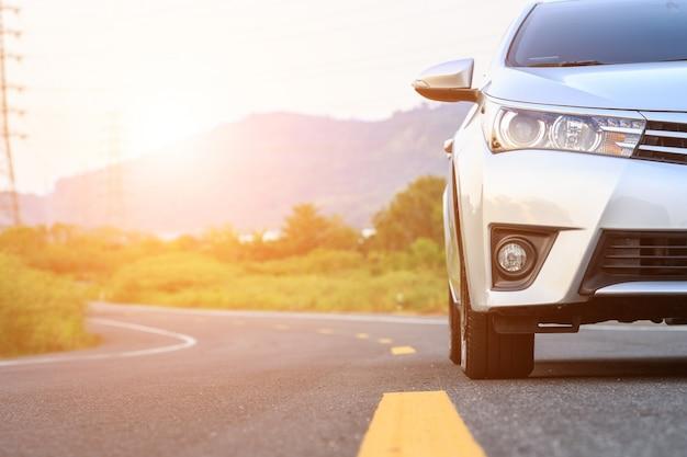 アスファルト道路に新しい銀車駐車場の正面 Premium写真