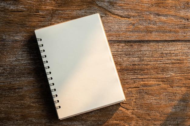 古い木の板に白い本のトップビュー Premium写真