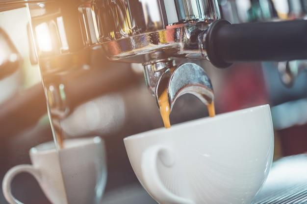 コーヒーの改ざんを押しながらコーヒーの準備をするバリスタの手 Premium写真