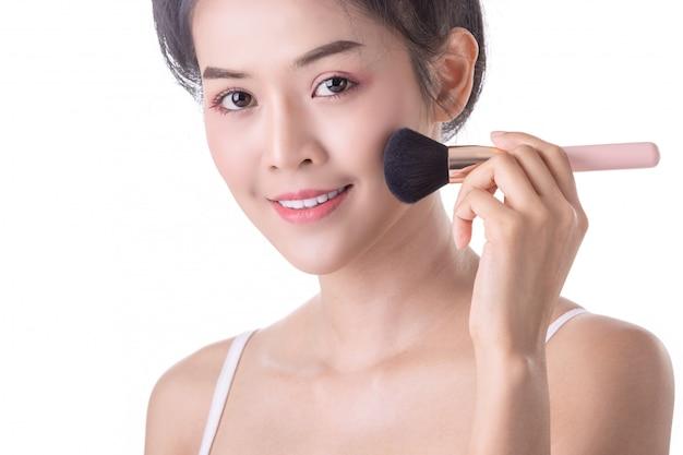 自分の顔に柔らかいブラシと化粧品を使用して美しい若いアジア女性。 Premium写真
