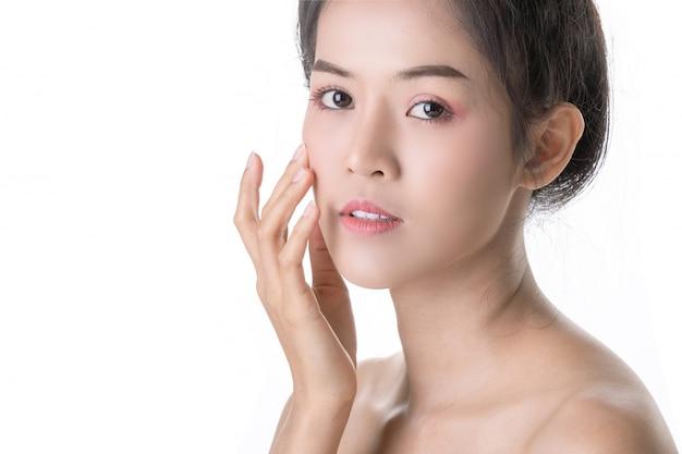 自分の顔に化粧品で美しい若いアジア女性 Premium写真