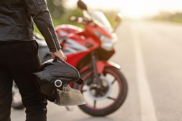 ハンサムなモーターサイクリストは、路上でヘルメットを保持している革のジャケットを着用 Premium写真