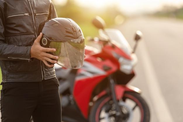 Красивый мотоциклист носит кожаную куртку, держа шлем на дороге Premium Фотографии
