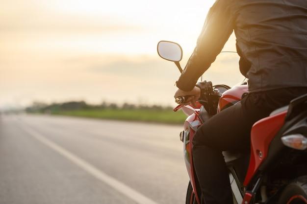 Красивый мотоциклист носит кожаную куртку сидя на мотоцикле на дороге Premium Фотографии