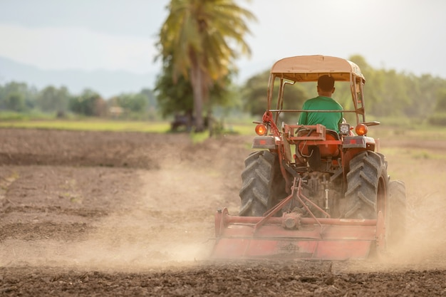 米の季節のために土を準備するために土地の大きいトラクターのタイの農民 Premium写真