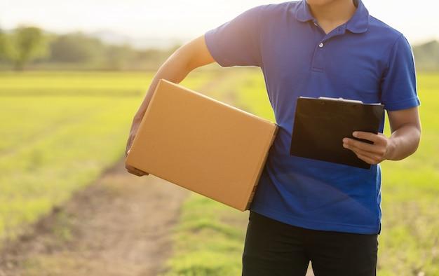配達人の田舎で顧客への茶色の小包または段ボール箱の配達を保持 Premium写真