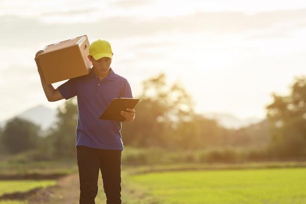 Доставка человек, держащий коричневые посылки или картонные коробки доставки до клиента в сельской местности Premium Фотографии