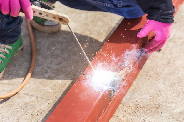 屋根の構造用鋼材を溶接する建設労働者 Premium写真