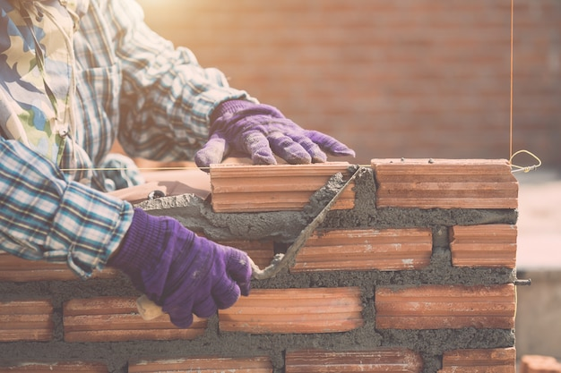 住宅建設の過程でレンガの壁を取り付ける労働者 Premium写真