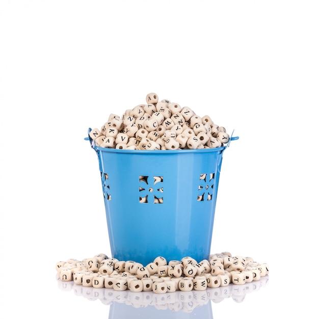 小さな青い金属製のバケツで木製アルファベットの山。 Premium写真