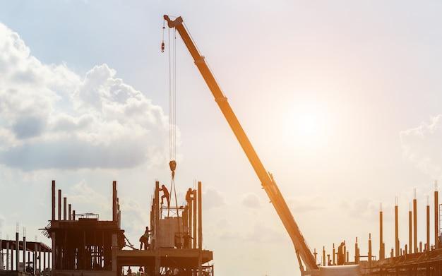 Силуэт строительный кран работает на сайте Premium Фотографии