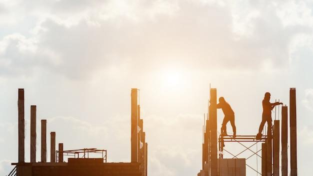 Силуэт строительных рабочих, работающих на сайте Premium Фотографии
