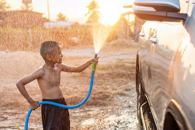 朝の時間で屋外で車を洗うにホースとスプレーから水を再生する幸せなアジア少年 Premium写真