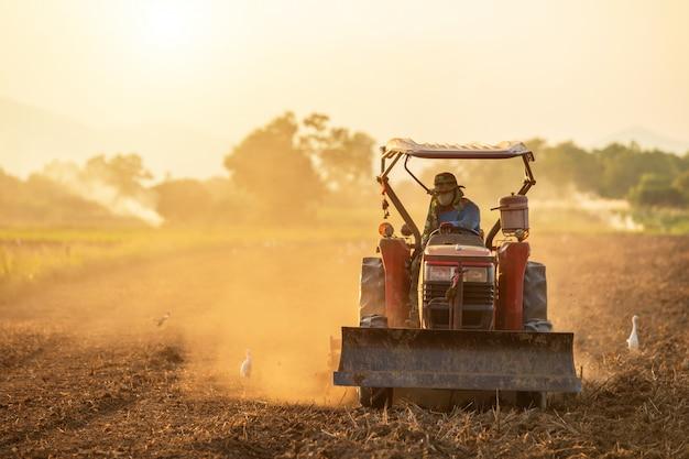土壌を準備する土地の大きなトラクターの農夫 Premium写真