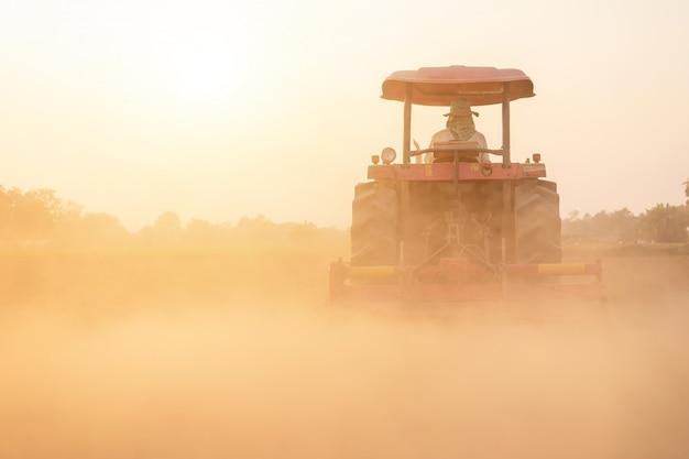 土を準備する土地の大きなトラクターでタイの農民 Premium写真