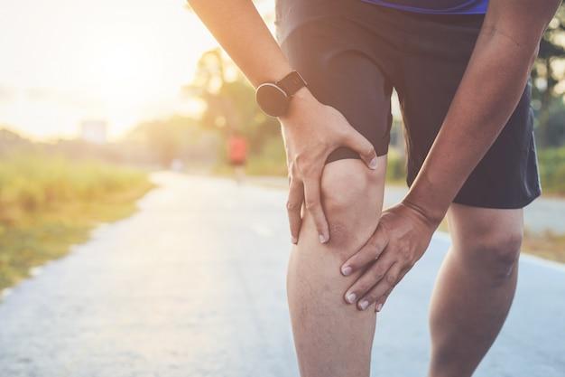 アジア人は公園の道を走っている間彼の膝を保持します。 Premium写真
