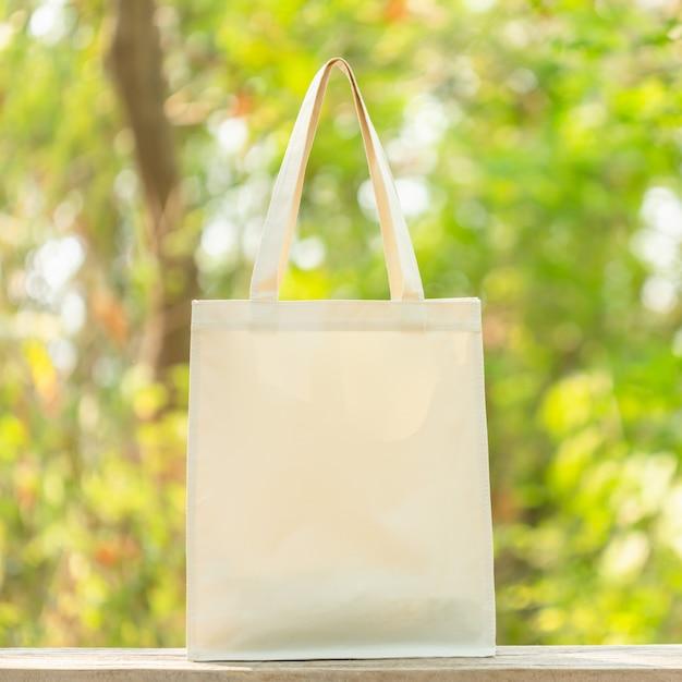 Белая сумка хлопка положить на деревянный стол с пространством для текста или рекламы. хлопковую сумку можно использовать для покупок, чтобы заменить полиэтиленовый пакет на зеленую природу Premium Фотографии