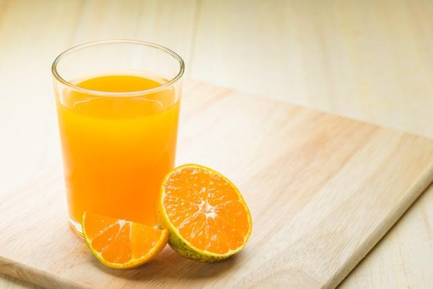 木製のベース、ガラスに隔離されたオレンジ Premium写真