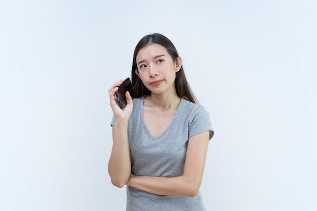 スマートフォンを持って考えている魅力的なアジアの女性 Premium写真