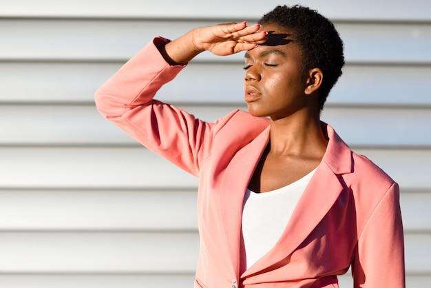黒人女性、都市の壁に立っているファッションのモデル Premium写真