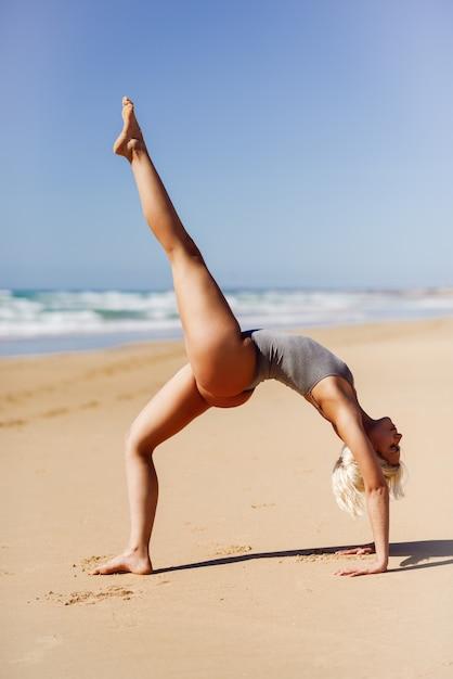 白人の金髪女性がビーチでヨガの練習 Premium写真