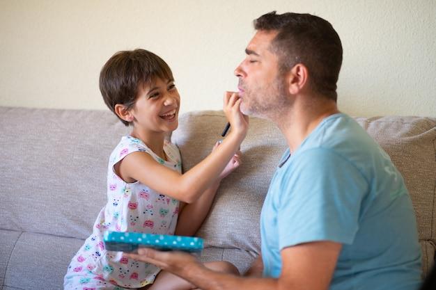 Маленькая милая дочь делает макияж для своего отца Premium Фотографии