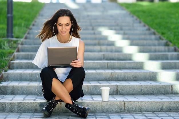 中年の実業家が床に座って彼女のラップトップコンピューターでの作業 Premium写真