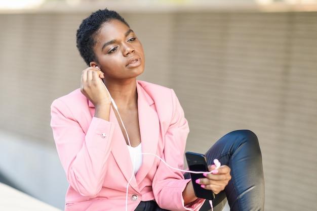 イヤホンでスマートフォンを使用して屋外に座っている黒の実業家 Premium写真