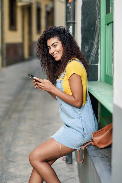 彼女のスマートフォンと屋外のテキストメッセージを座っているアフリカの女性 Premium写真