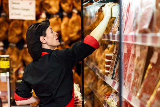 精肉店で製品を服用している女性労働者の肖像画 Premium写真