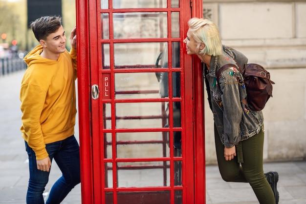 古典的なイギリスの赤い電話ボックスの近くの友人の若いカップル Premium写真