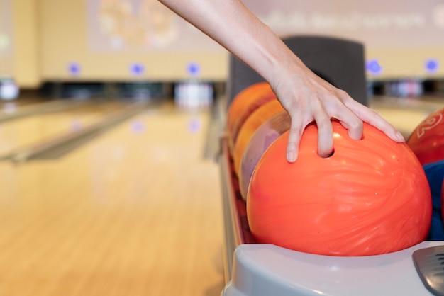 ボーリング場に対してスタックからボウリングボールを持つ女性の手にクローズアップ Premium写真