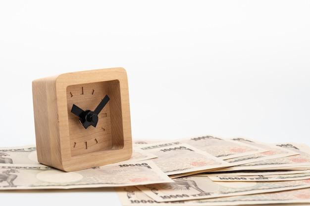 日本の通貨円お金紙幣の小さな正方形の木製時計を閉じます。日本経済と投資。 Premium写真