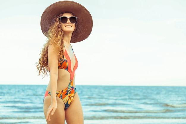 Счастливая молодая женщина на пляже в летние каникулы. Premium Фотографии
